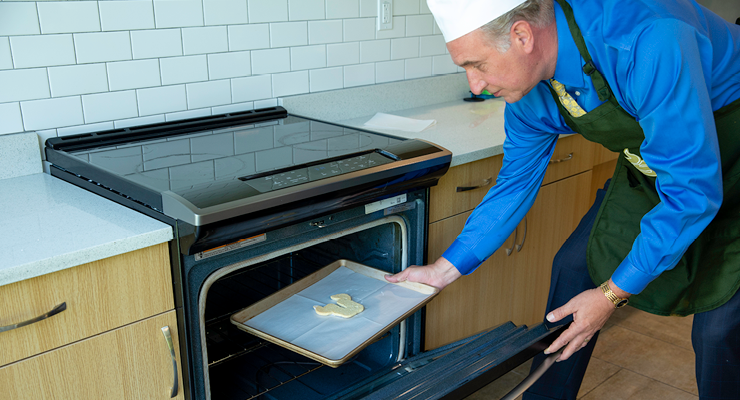 Dean Besterfield places the Bull U cookie in the oven to bake
