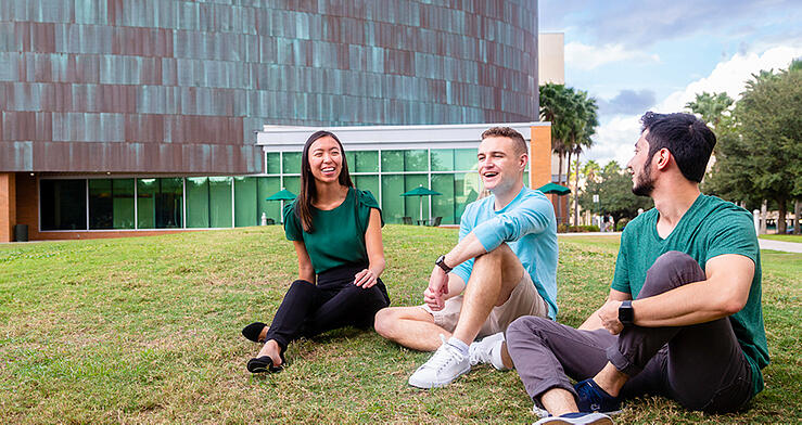 Three USF students sit on the lawn in front of the Marshall Student Center