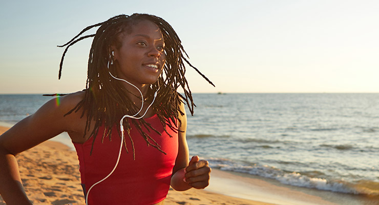 Female student running and listening to music on the beach to reduce stress.