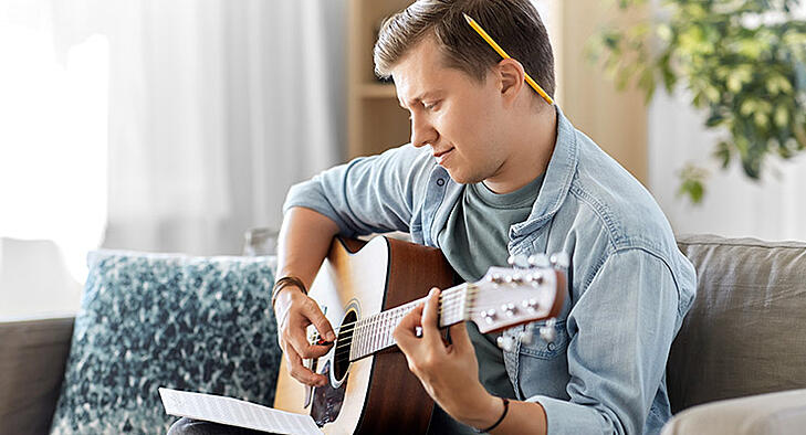 Male college student playing guitar to reduce stress.