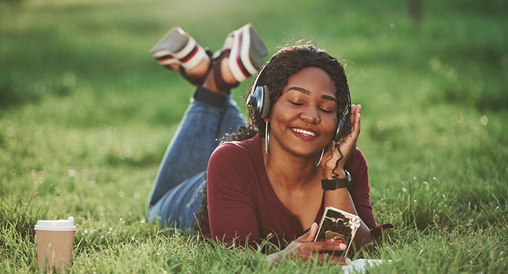 Female student listening to music outside finding ways to have summer break fun while social distancing.