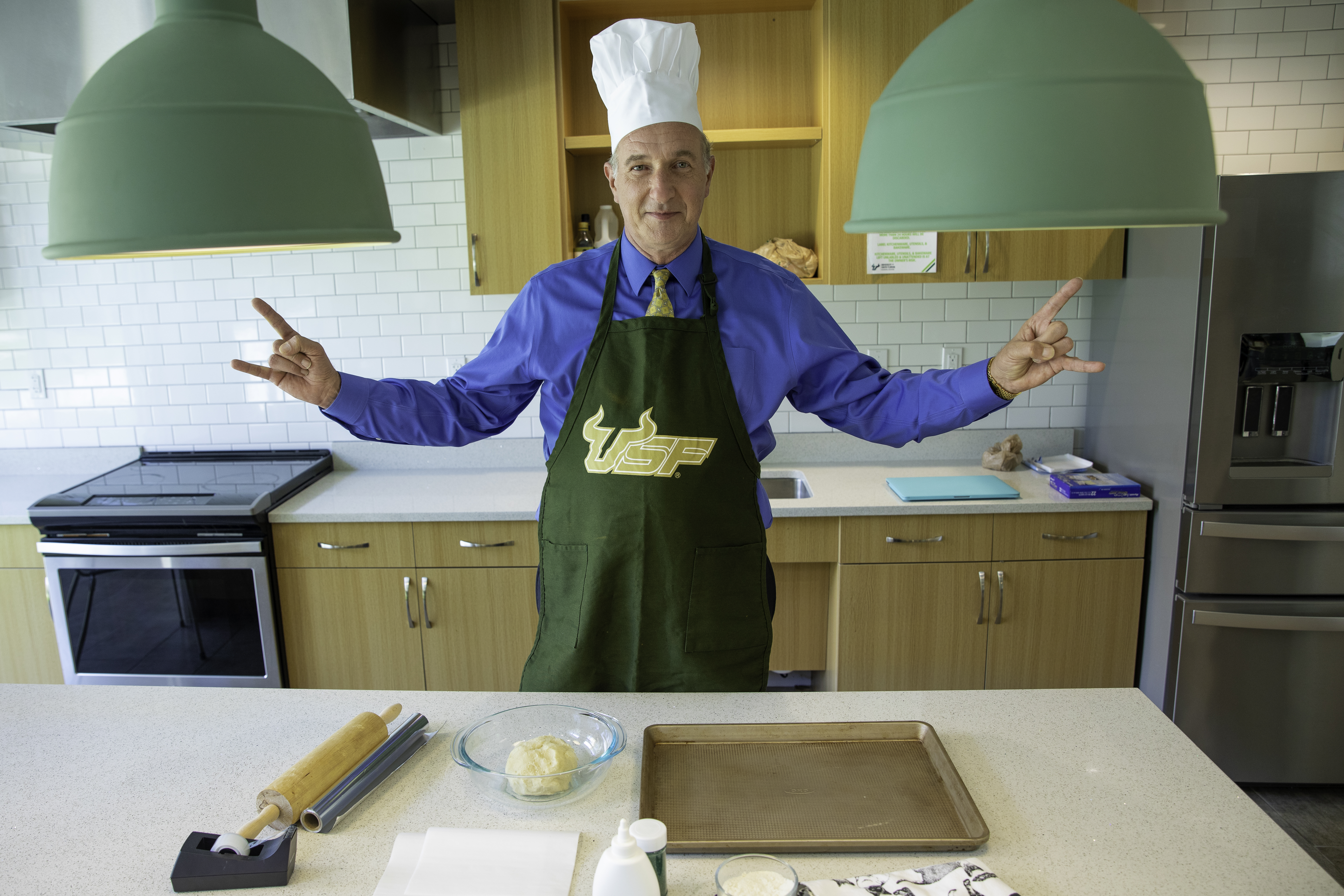 """Dean Besterfield gives the """"Go Bulls!"""" hand sign in a kitchen"""