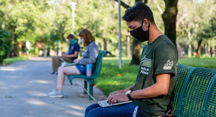 Male USF student chatting with his parents on his laptop about COVID-19 while on campus.
