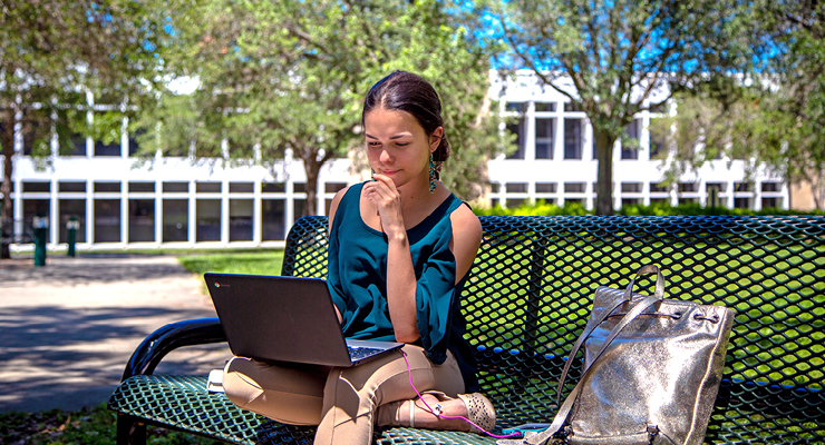 Female student researching the benefits of starting college in the spring or summer semesters on her laptop outside.