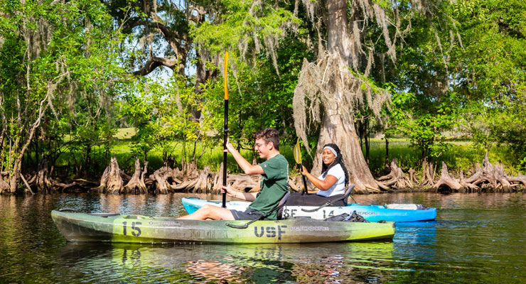 Two students paddle down the Hillsborough River in USF kayaks.