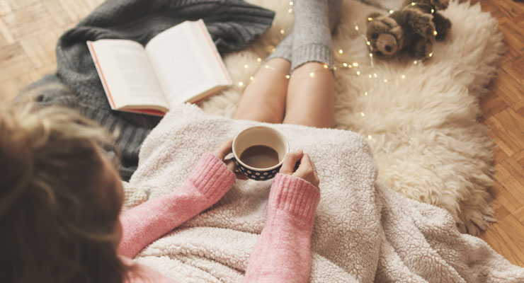 A young woman sits on a blanket with a book and cup of tea.