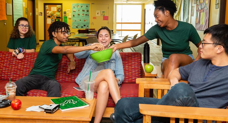 A group of students share a bowl of snacks in a residence hall.