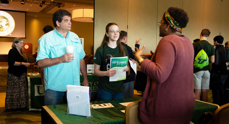 Student and parent talk to a USF representative at a college fair event.