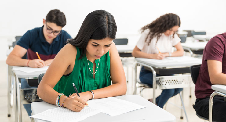 Four students take the ACT exam in a classroom