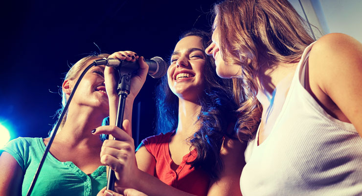 Three female college students in front of a microphone singing karaoke