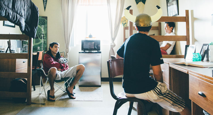 Three USF students talk to each other in a residence hall room.