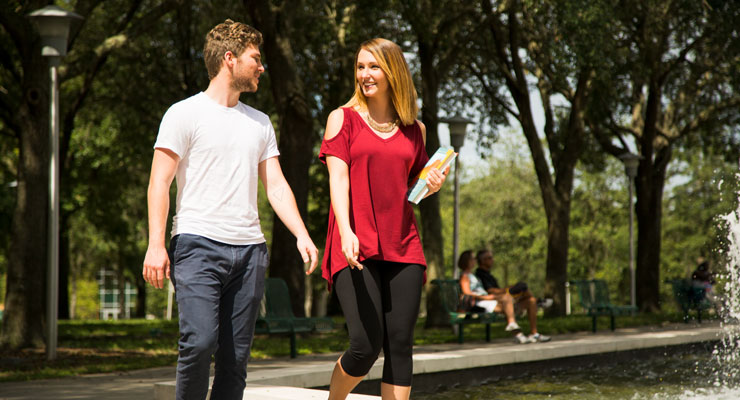 One male and one female student walking across the USF Tampa campus