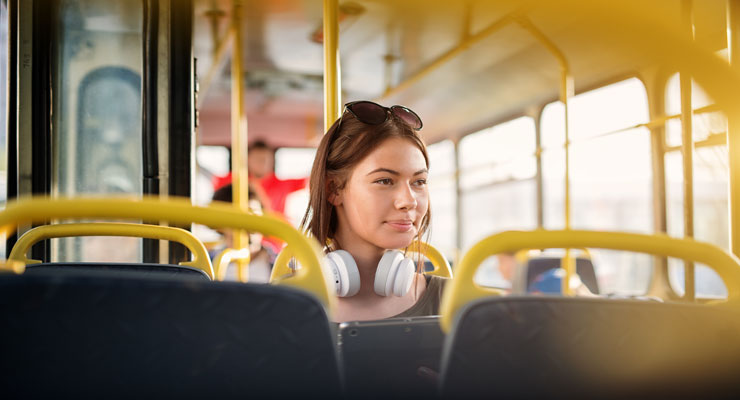 A young woman riding public transportation to her college campus