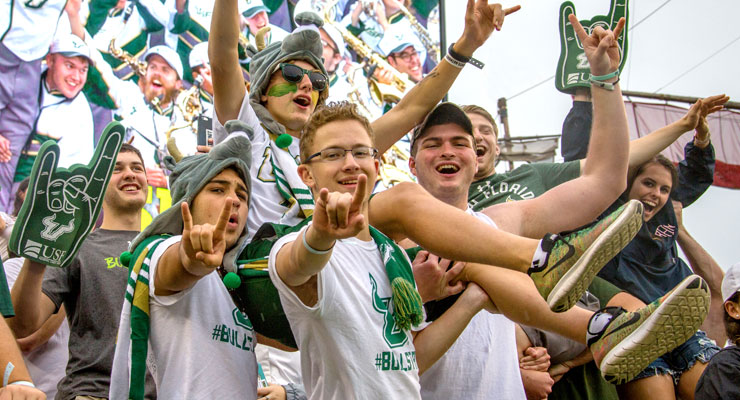 A group of students cheering on the USF Bulls football team from the stands