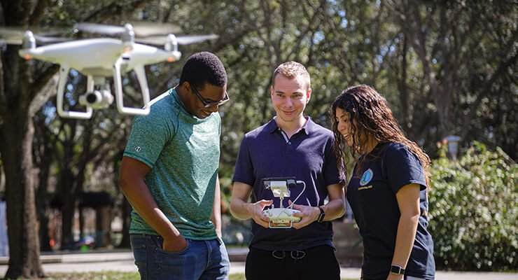 National Merit Scholars at USF participating in research using a drone.