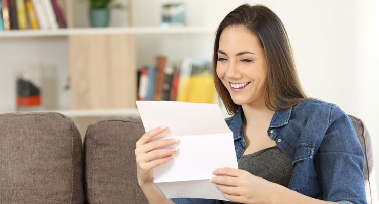 A high school student sitting on her couch at home reads her collage application response letter