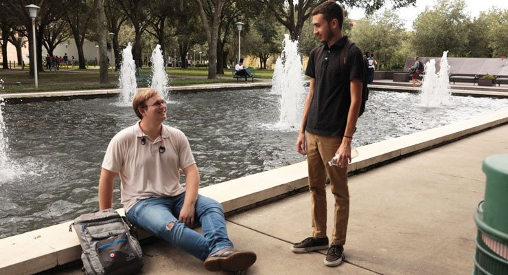 Two USF students talk and enjoy being outside at the MLK Plaza.
