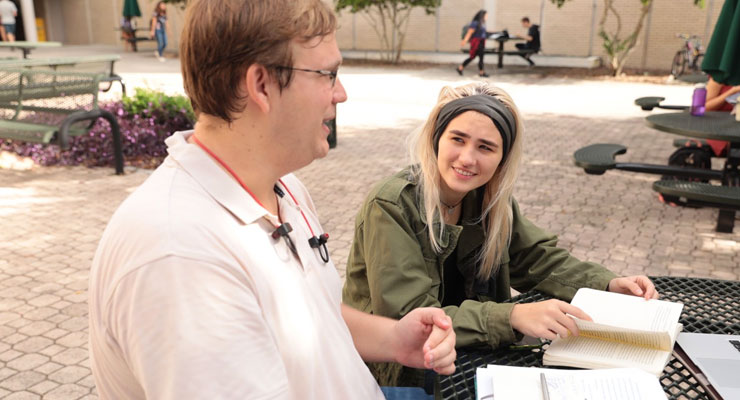Two USF students discuss assignments for a class.
