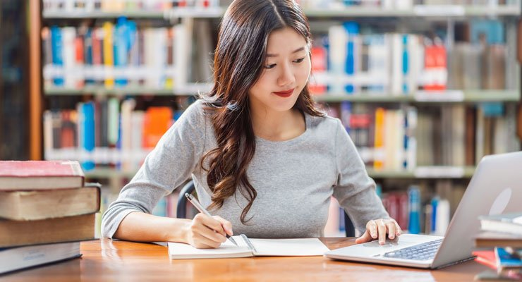 A female student sitting at a table in the library working on college decisions on her laptop