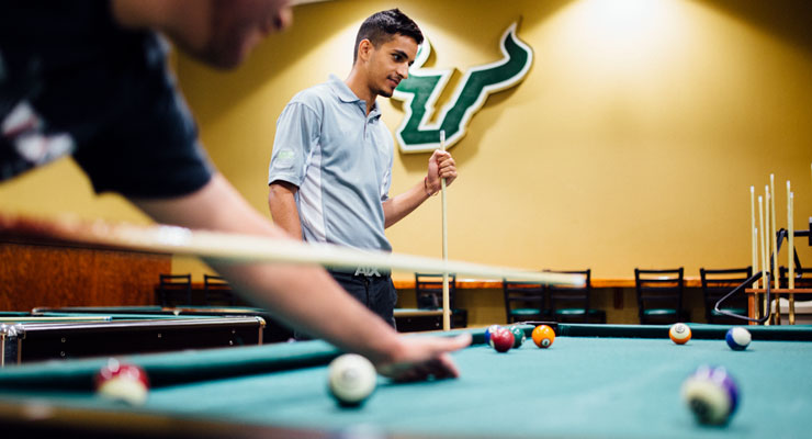 USF students playing a friendly game of pool.