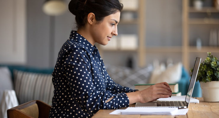 A female student fills out scholarship applications on her laptop