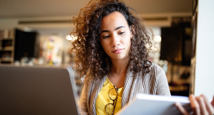 female student in a yellow shirt studies in the library
