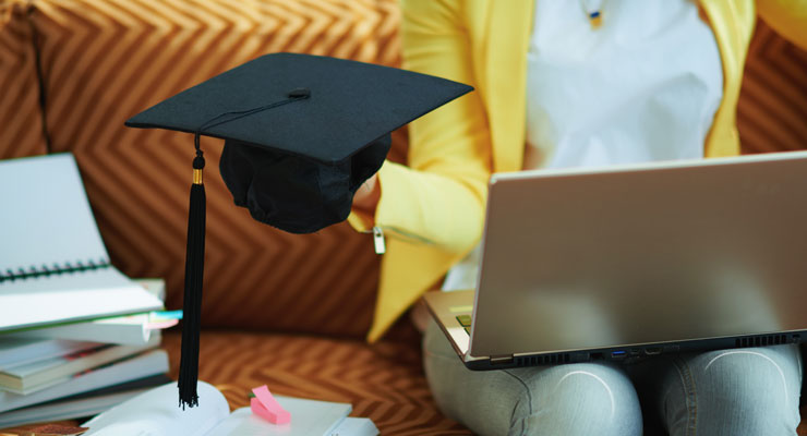a student holds her mortarboard and tassel while celebrating her virtual high school graduation on a Zoom call