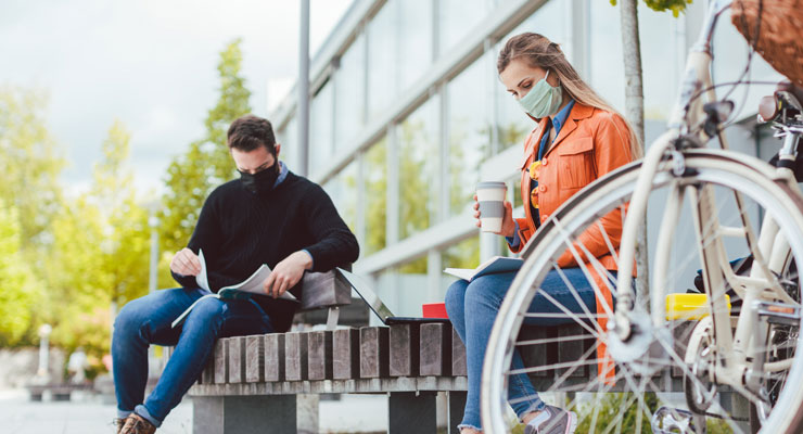 two students in masks begin the transition from high school to college by relaxing on a campus bench