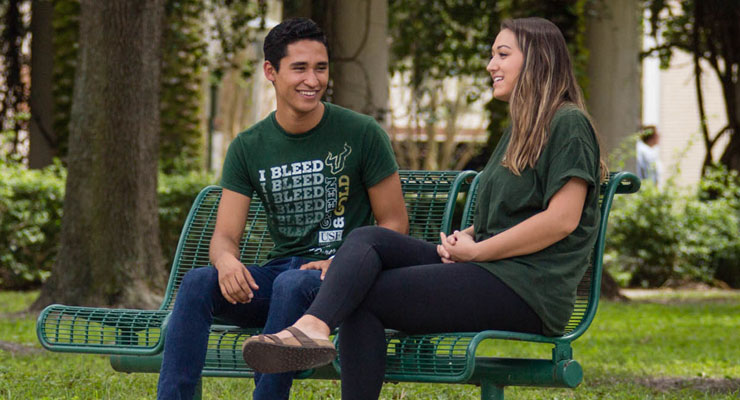 USF students sitting on a bench and talking
