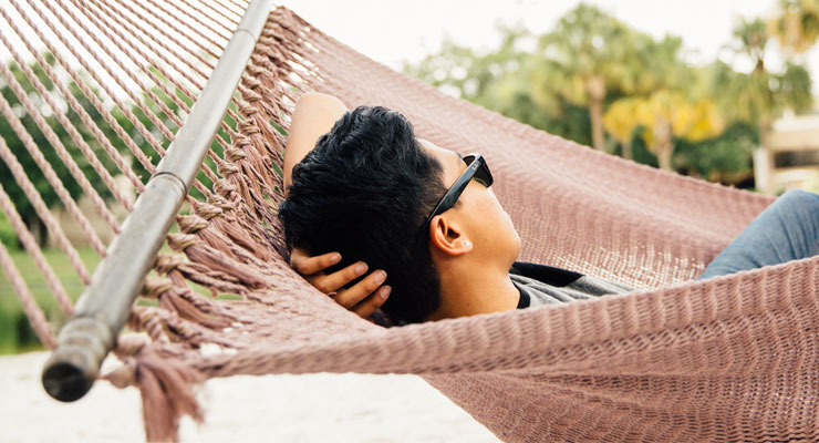 USF student relaxing in a hammock at Castor Beach on campus.