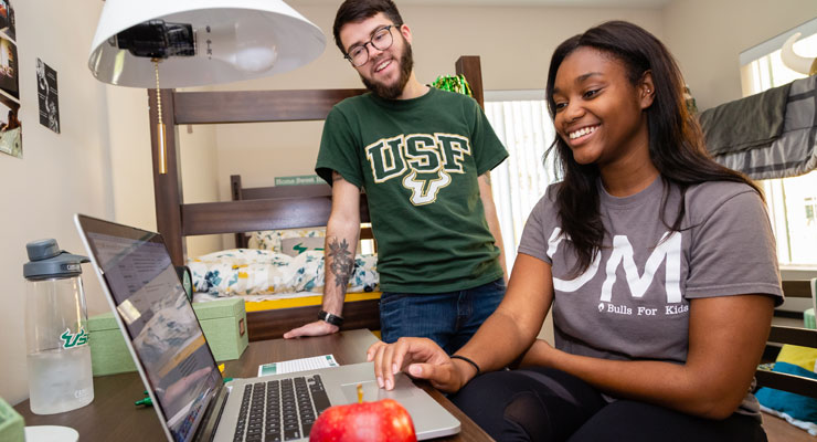 Two USF students studying life skills they need for college in their dorm room.