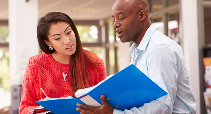 College counselor going over paperwork with a student