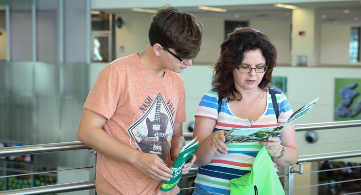 A mother and son reading USF materials at an open house event