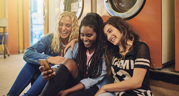 Three college women look at a cell phone together and laugh while waiting for their laundry to finish