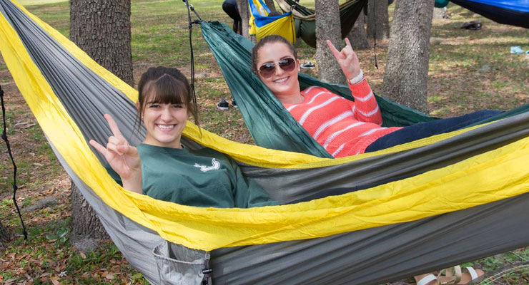 USF students relaxing in hammocks outside on campus.