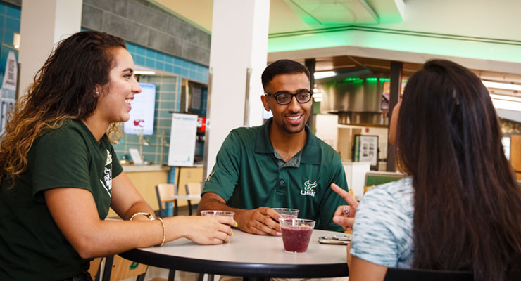 Three USF college students talk about their part-time jobs while at a dining hall