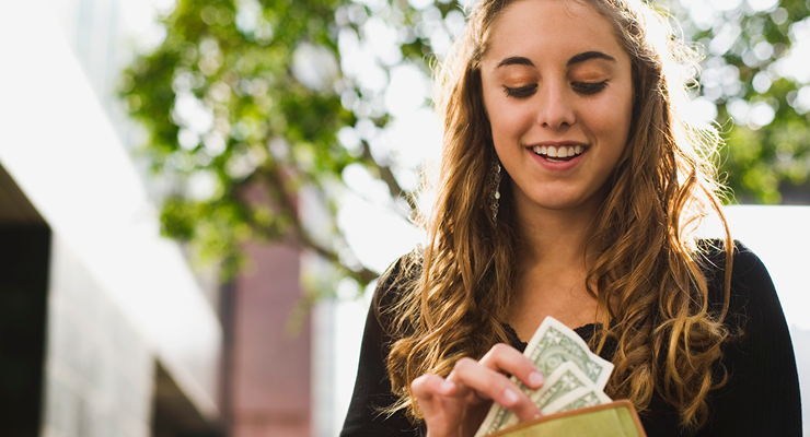 A high school student smiles as she pulls cash out of her wallet