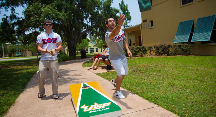 USF students play a game of corn hole outside of Greek Village.