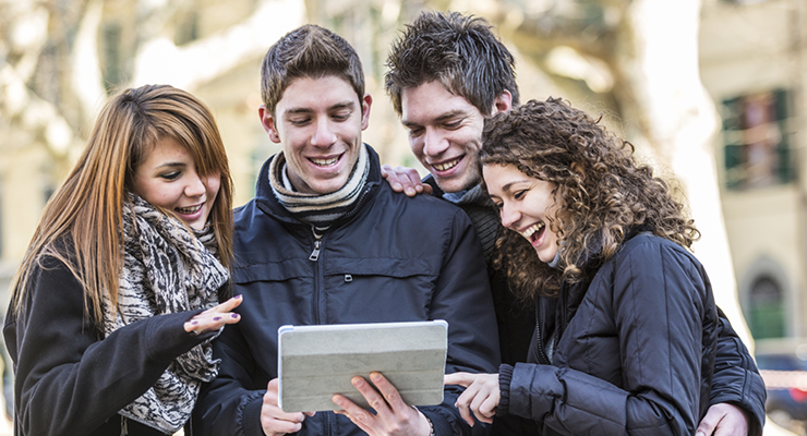 Four students looking at a tablet and smiling.
