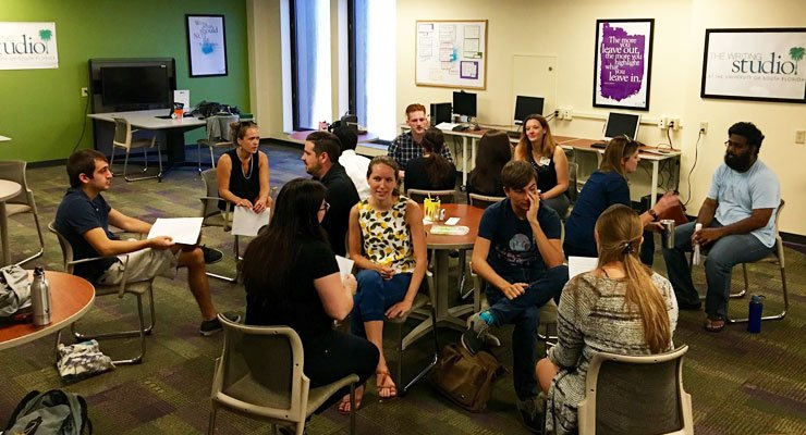 USF classmates discuss their classwork together in a large room