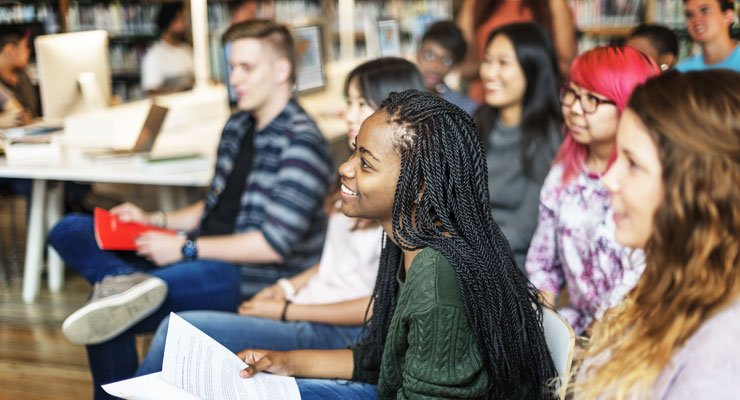 College students smile as they watch a lecture