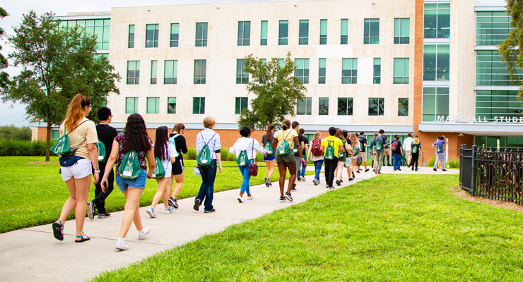 Prospective USF students and families take a campus tour and walk towards the Marshall Student Center.