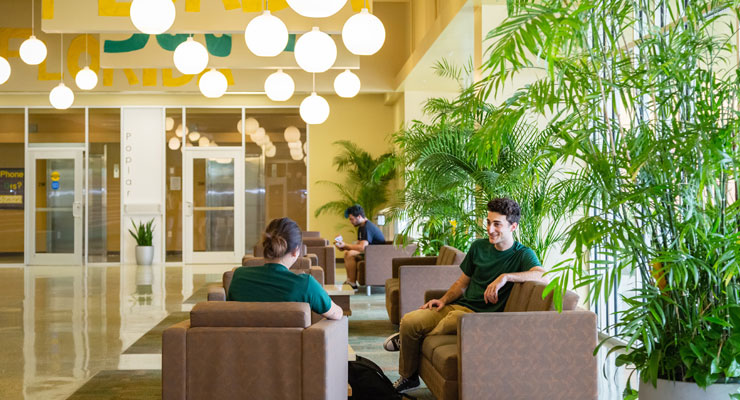 USF students talk in the lobby of Juniper-Poplar Hall, an on-campus residence hall