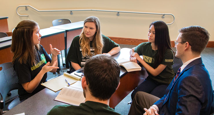 Five USF students work on a class assignment together
