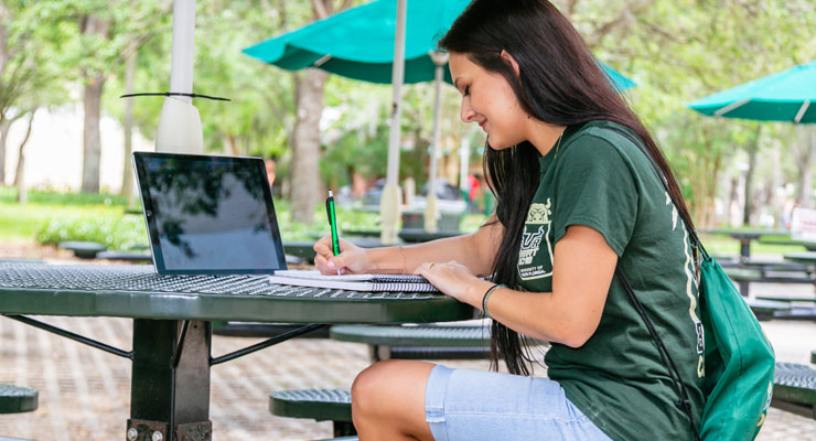 A USF student writes in a notebook as she sits at a table outside