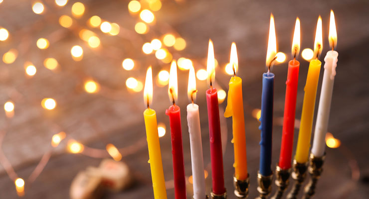 Nine lit Hanukkah candles in shades of yellow, red, white and blue in a brass menorah