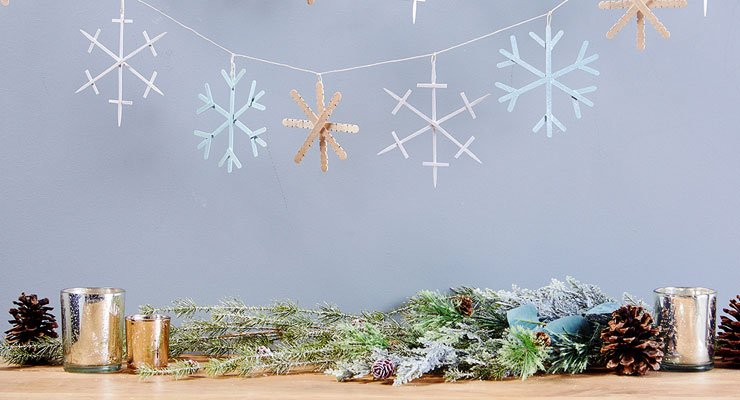 DIY snowflake garland on a string, holiday greens, pine cones and votive candles