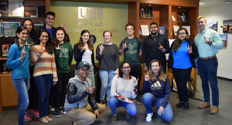 USF Honors College students standing next to the Honors College sign.