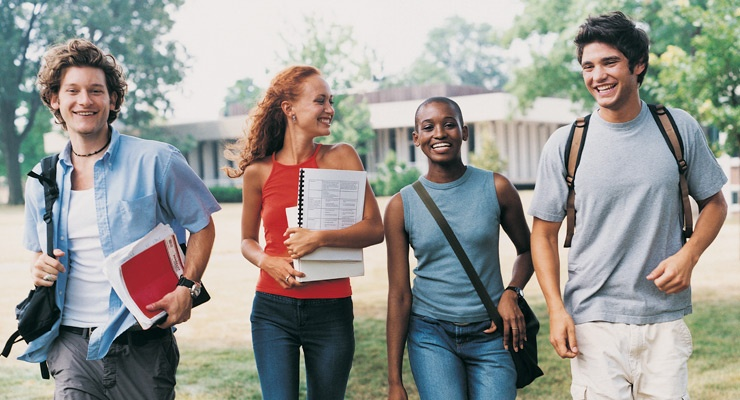 A group of four high school students with books walk together and smile.