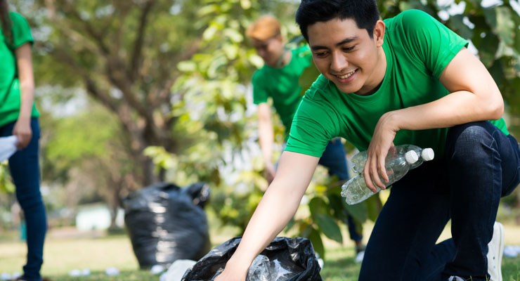 A student participates in a volunteer activity and helps pick up trash at a park.